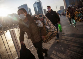 People wear face masks as they walk outside a bus terminal following an outbreak of the coronavirus disease (COVID-19) in Beijing, China, December 10, 2020.   REUTERS/Thomas Peter