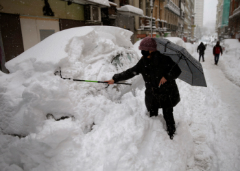 A woman tries to remove the snow from her car during a heavy snowfall in downtown Madrid, Spain, Saturday, Jan. 9, 2021. A persistent blizzard has blanketed large parts of Spain with 50-year record levels of snow, halting traffic and leaving thousands trapped in cars or in train stations and airports that suspended all services as the snow kept falling on Saturday. (AP Photo/Andrea Comas)