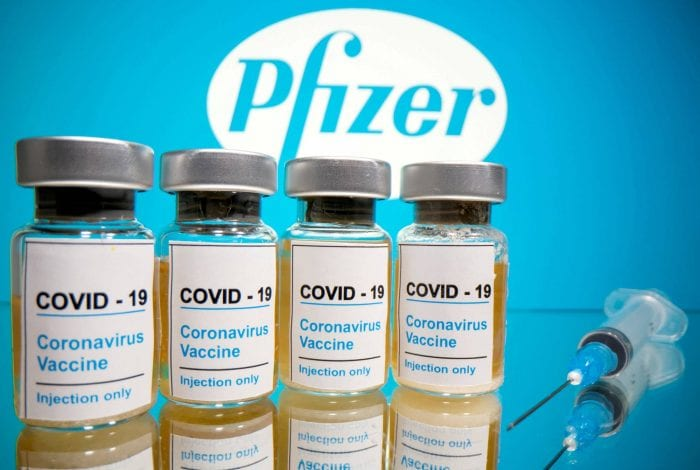 "FILE PHOTO: Vials with a sticker reading, ""COVID-19 / Coronavirus vaccine / Injection only"" and a medical syringe are seen in front of a displayed Pfizer logo in this illustration taken October 31, 2020. REUTERS/Dado Ruvic/File Photo"